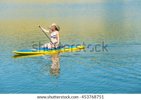Young woman learning how to paddleboard on small pond.