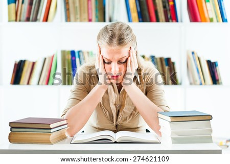 Young woman learning in library,she is tired