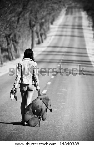 Young woman left behind with her teddy bear. - stock photo