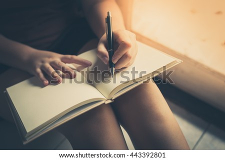 Young woman left hand writing on blank book while sitting beside window in morning time on weekend. Morning lifestyle on weekend concept with vintage filter effect - stock photo