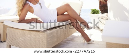 Young woman legs in a fashion club sun lounger on a beach. - stock photo