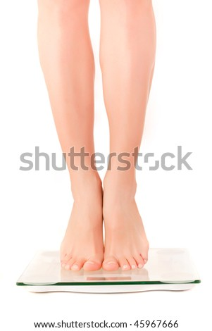 Young woman legs on scale. Over white background