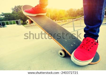 young woman legs skateboarding at skatepark  - stock photo