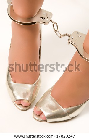 Young woman legs with handcuffs isolated on white - stock photo