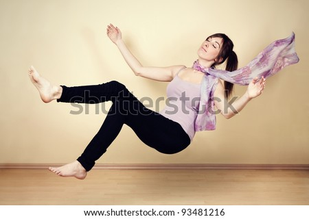 Young woman levitating in empty room - stock photo
