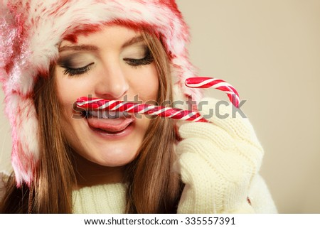 Young woman licking sweet candy cane. Girls hands in woolen white gloves having fun. Christmas time concept. - stock photo
