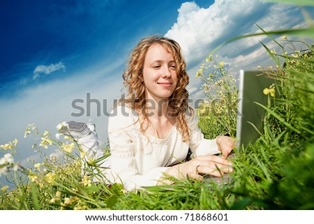 Young woman lie grass with a laptop. Against blue sky. - stock photo