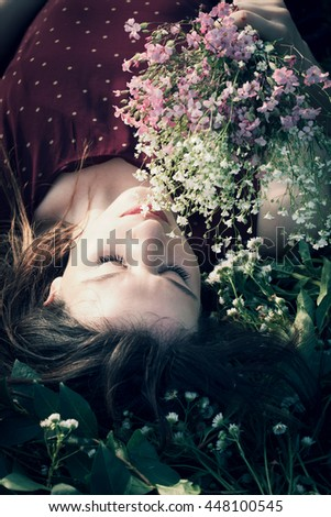 young woman lie in grass hold flowers beautiful summer day in nature - stock photo