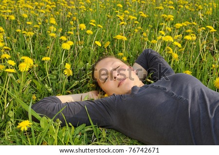 young woman lies on a flower meadow - stock photo