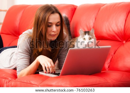 Young woman lies on the red sofa with cat and working laptop - stock photo