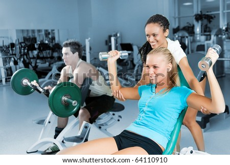 Young woman lifting a dumb-bell in the gym assisted by her personal trainer - stock photo