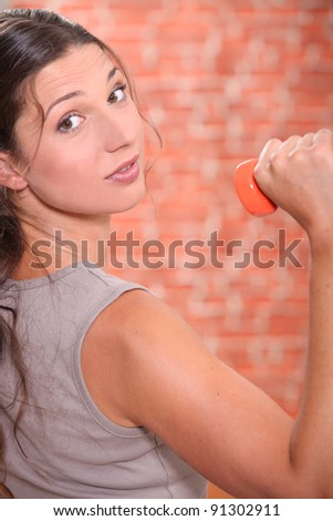 Young woman lifting dumbbell - stock photo