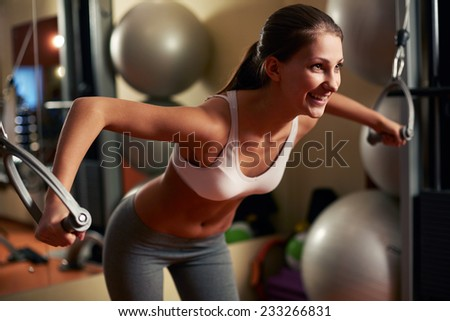 Young woman lifting weights at home gym - stock photo