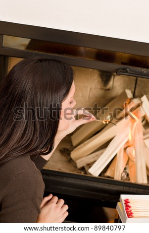 Young woman lighting up wood logs in fireplace home living