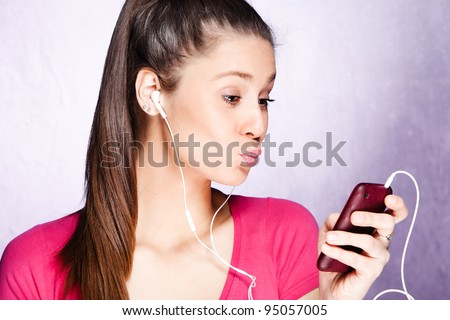 young woman listen music from cell phone with earphones, studio shot - stock photo