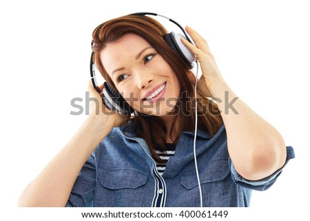 Young woman listen to music on her headphones, isolated over white background - stock photo
