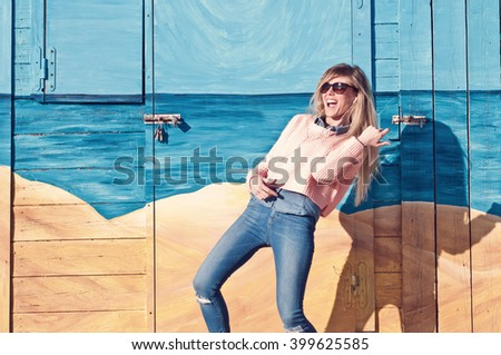 Young woman listen to music with headphones and imitating the guitar