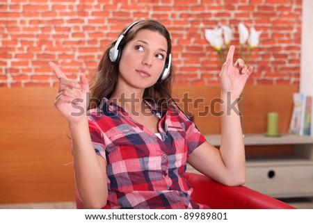 young woman listening music at home - stock photo