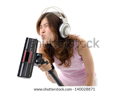 Young woman listening music in headphones and doing housework. Asian female.