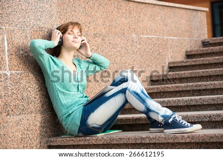Young woman listening music in Headphones. Beautiful young female student.  Woman sitting on stairs in city park. - stock photo