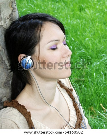 Young woman listening music in the park