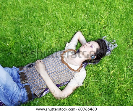 Young woman listening music in the park - stock photo