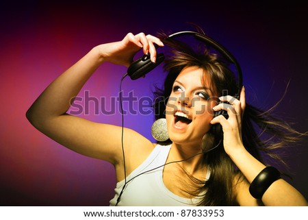 young woman listening music on gradiant background - stock photo