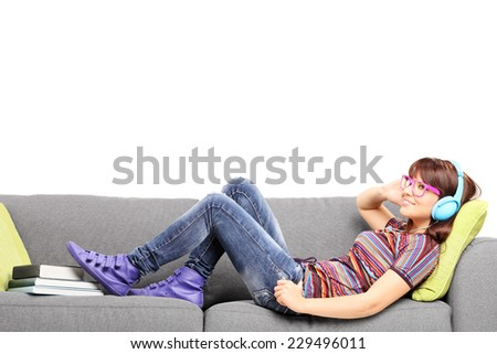 Young woman listening music on headphones and lying on a couch isolated on white background - stock photo