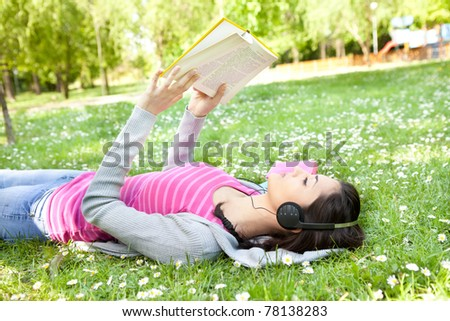 young woman listening music on the grass using headphones and reading book - stock photo