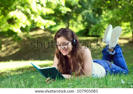 young woman listening music through headset and reading book in park