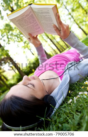 young woman listening music through headset and reading book in park - stock photo