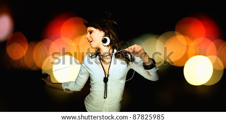 young woman listening music with bokeh effect on background