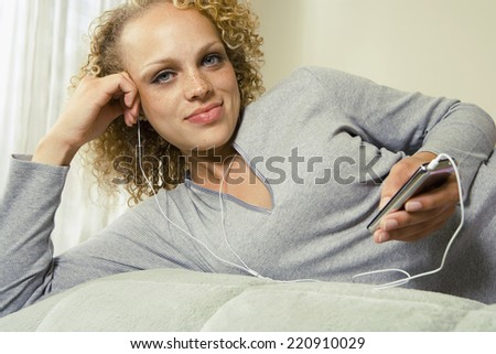 Young woman listening to mp3 player in bed