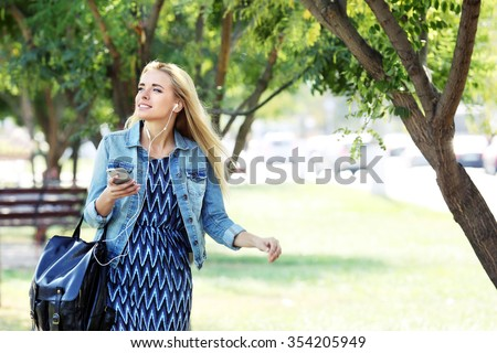 Young woman listening to music and walking in the park - stock photo