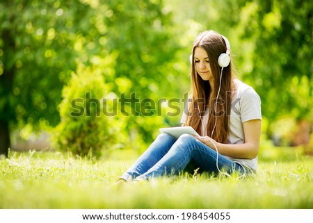 Young woman listening to music in a lush park sitting on the grass with her tablet on her knees selecting a tune to listen to on her headphones - stock photo