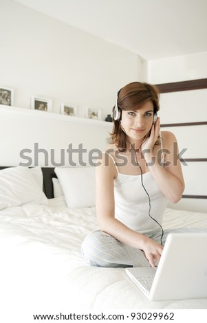 Young woman listening to music in bed, using a laptop computer and headphones.