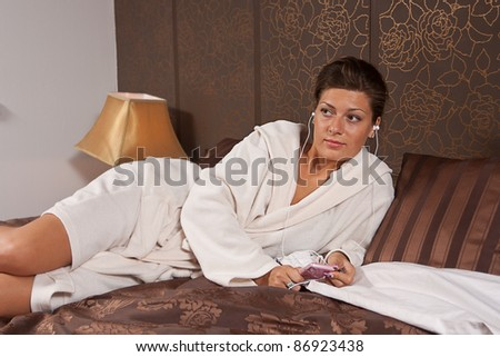 Young woman listening to music lying on a bed - stock photo