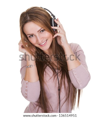 Young Woman Listening To Music On Headphone Over White Background - stock photo