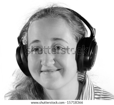 Young woman listening to music on headphones. Isolated on white - stock photo