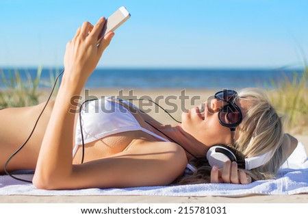 Young woman listening to music on headphones on the beach - stock photo