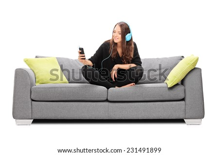 Young woman listening to music on her phone seated on a sofa isolated on white background - stock photo