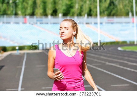 Young woman listening to music on the stadium - stock photo