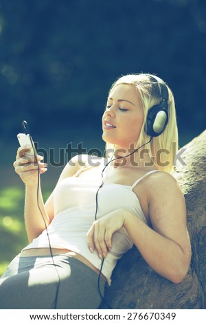 Young woman listening to music or audio book with headphones - stock photo