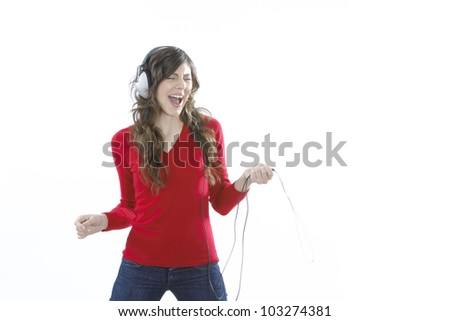 Young woman listening to music, singing and dancing to the rhythm. - stock photo