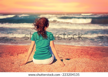 Young woman listening to music with headphones while sitting on the beach and looking at the stormy sea - stock photo