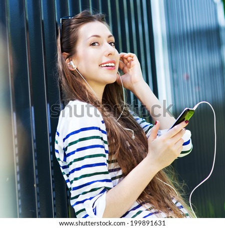 Young woman listening to music with smartphone - stock photo