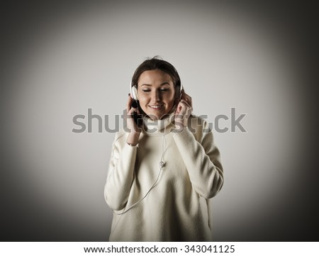 Young woman listening to music. Young woman is doing something. - stock photo