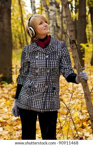 Young woman listening with headphones in autumn forest - stock photo