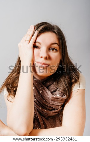 Young woman listens to a boring story. On a gray background. - stock photo