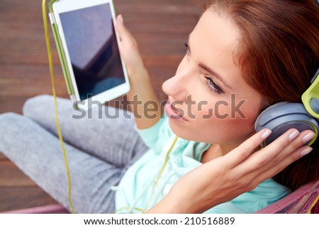 Young woman listens to music on tablet - stock photo